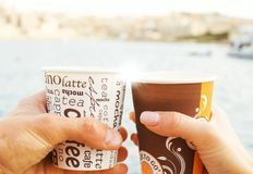 A young couple  is holding cups of coffee in front of sea and blurred view ,love story ,close up. A young couple a man and woman ,holding cups of coffee in front Royalty Free Stock Images