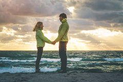 Young Couple Man and Woman holding hands in Love. Romantic Outdoor with sea and sunset sky nature on background Lifestyle Feelings relationship concept Stock Image
