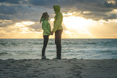 Young Couple Man and Woman holding hands in Love. Romantic Outdoor with sea and sunset sky nature on background Lifestyle Feelings relationship concept Royalty Free Stock Image
