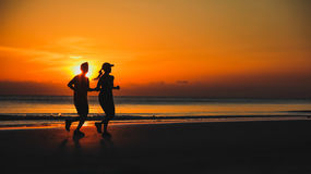 Young couple: man and woman run together on a sunset on lake Stock Photos