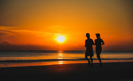 Young couple: man and woman run together on a sunset on lake Stock Photo