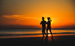 Young couple: man and woman run together on a sunset on lake Stock Image