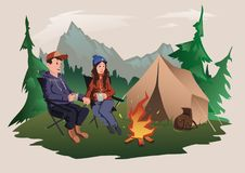 Young couple, man and woman sitting around the campfire in the forest. Hiking, active outdoor recreation. Isolated. Young couple, man and woman sitting around Royalty Free Stock Images