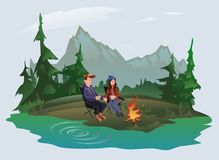Young couple, man and woman sitting around the campfire in the woods on the shore of the lake. Hiking, active outdoor. Young couple, man and woman sitting around Stock Photography