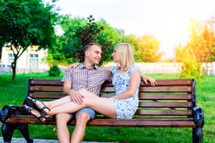 Young couple man and woman sitting on a bench hugging in park ribbon,  declaration of love,  gentle hug, the concept  ev Stock Photography