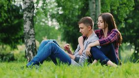 Young couple man and woman sitting on the grass in the park, enjoy the tablet. Girl pressed against the guy stock video