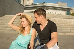 A young couple are sitting on the steps near a high-rise building on a sunny summer day. They communicate with. A young couple , men and a woman, are sitting on royalty free stock photos
