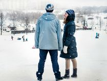 Young couple man and woman standing against winter landscape royalty free stock images