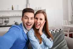 Young couple together at home weekend taking selfie pictures happy stock images