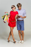 Young couple with many bags and empty wallet Royalty Free Stock Photos