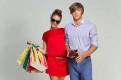 Young couple with many bags and empty wallet Royalty Free Stock Images