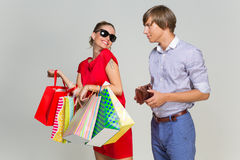 Young couple with many bags and empty wallet Stock Images