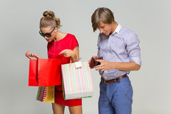 Young couple with many bags and empty wallet Stock Photography