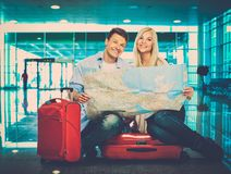 Young couple with map in airport Royalty Free Stock Photography