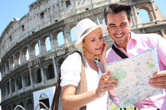 Young couple with a map standing near Coliseum of Rome. Tourists reading map in front of the Coliseum, Rome Royalty Free Stock Image