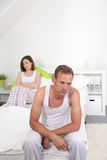 Young couple with marital problems. Sitting on a bed ignoring each other and sulking after an argument, each sitting staring despondently ahead Stock Photos