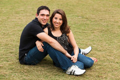 Young Couple. Young married couple  in a loving pose sitting on a lawn in a park Royalty Free Stock Image