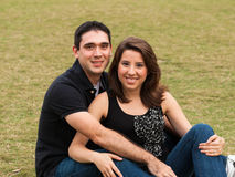 Young Couple. Young married couple  in a loving pose sitting on a lawn in a park Royalty Free Stock Images