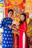 Young couple with a mask of lion. Young couple in ao dai dresses holding a mask of lion Stock Photos