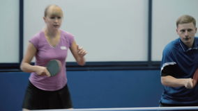 Young couple masterfully playing the tennis at the court. Close-up. Young woman and man together playing a table tennis on the one side. The couple quickly hits stock video