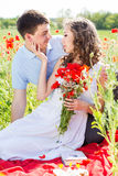Young couple on a meadow full of poppies Royalty Free Stock Photography