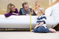 Young couple measuring bed in furniture shop, smiling at daughter (6-8) Royalty Free Stock Images