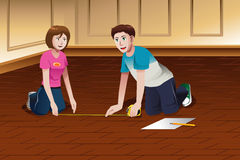 Young couple measuring floor Royalty Free Stock Image