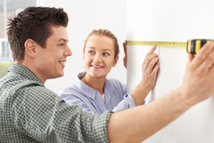 Young Couple Measuring Wall In New Home Royalty Free Stock Photo