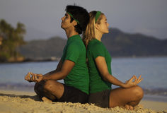 Young couple meditating. On the beach at sunrise in hawaii Stock Image