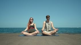 Young couple meditating sitting on pier by beach. Holidays with yoga classes stock video footage
