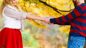 Young couple meet in park on date holding hands. Stock Image