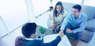 Young couple in meeting with a financial adviser. High angle view of a smiling young couple in meeting with a financial adviser at home Stock Photo