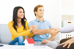 Young couple meeting with real estate agent at home. Young couple meeting with real estate agent or financial adviser at home royalty free stock photo