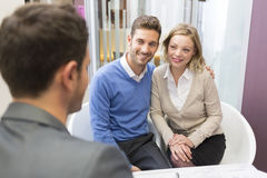 Young couple meeting real-estate agent for house investment. Husband and wife looking at a presentation with an adviser in an agency royalty free stock images