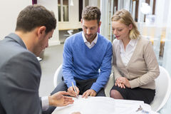 Young couple meeting real-estate agent for house investment. Signing a contract. Husband and wife signing a contract with an adviser in an agency stock photo