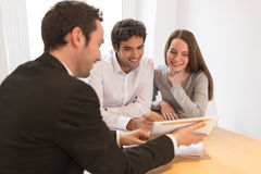 Young Couple meeting real-estate agent to buy property. Woman men advisor office house investment royalty free stock photography