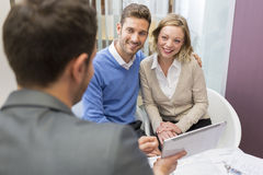Young couple meeting real-estate showing a investment project on. Husband and wife looking at a presentation with an adviser in an agency Royalty Free Stock Images