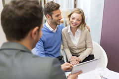 Young couple meeting real-estate showing a investment project on. Husband and wife talking with an adviser with tablet Royalty Free Stock Photography