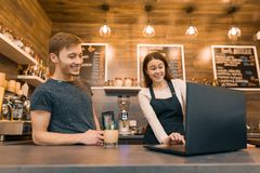 Young couple man and woman owners of small modern coffee house using laptop computer for work royalty free stock photo