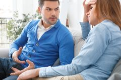 Young couple waiting for psychology session family problems quarelling close-up. Young couple men and women waiting for psychology session sitting on sofa close royalty free stock image