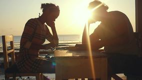 Young couple with menu and smartphones in beach cafe during sunset time. Slowmotion. 1920x1080 stock video footage