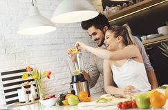 Young couple mixing fruit in a food processor Royalty Free Stock Image