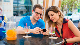 Young couple with mobile phone in cafe. Stock Photos