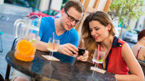 Young couple with mobile phone in cafe. Royalty Free Stock Images