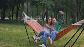 Young couple with mobile phone sitting on hammock. Fall from the hammock to the grass stock footage