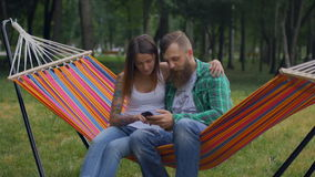 Young couple with mobile phone sitting on hammock. Romantic couple using smartphone in hammock stock video footage