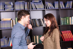 Young Couple with Mobile Phone Talking at Library stock image