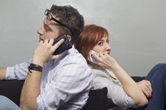 YOUNG COUPLE WITH MOBILE PHONES Royalty Free Stock Photography