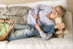 Young couple with mobile phones on sofa, woman embracing man's legs, smiling, portrait, elevated view Royalty Free Stock Photography