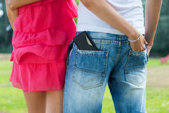 Young couple with mobile in the pocket. Stock Photo